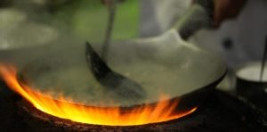 Closeup shot of a chief making a delicious dish for the guests in a pot