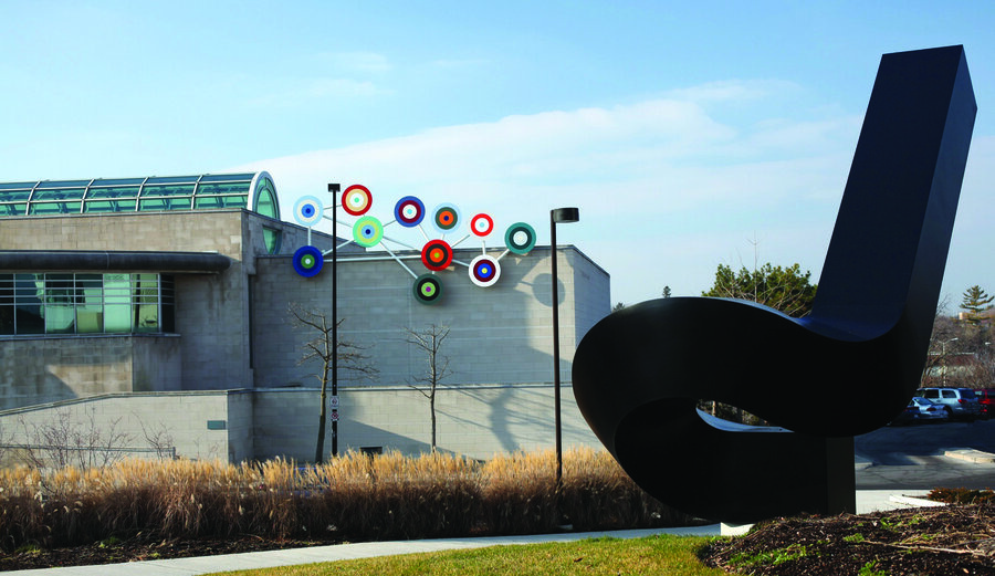 """Exterior photo of The Robert McLaughlin Gallery in Oshawa, showing exterior exhibits """"Group Portrait 1957"""" by Douglas Coupland and """"Upstart II"""" by Clement Meadmore"""