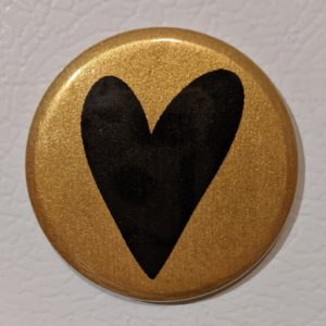 Photo of the author's wedding logo; black heart over a gold circle