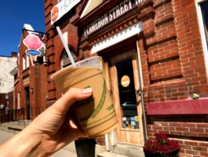 Close up of an iced coffee in a person's hand in front of Holy Grounds Café in Cannington.