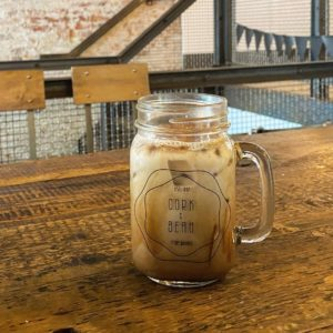 Iced coffee in a mason jar sitting on a table at Cork & Bean.