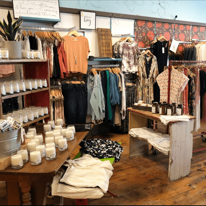 Gather store interior with clothing hanging on racks.
