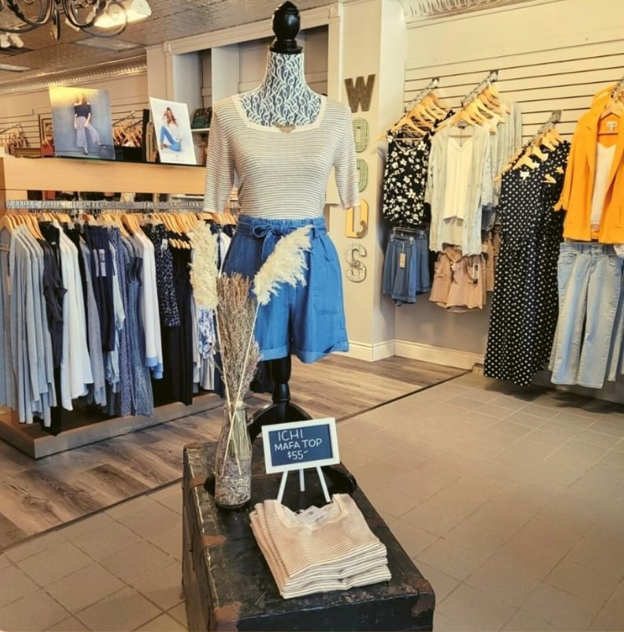 Clothing displayed on mannequin at entrance of Woods Clothing.