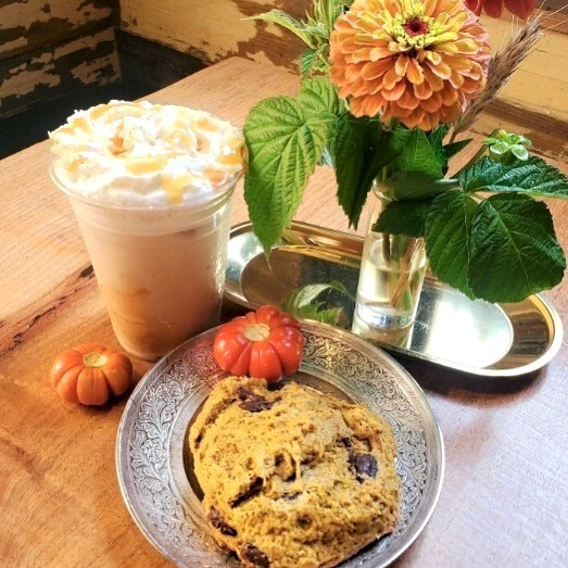 Pumpkin pie iced latte and a pumpkin chocolate scone sitting on a table with a vase of orange flowers.